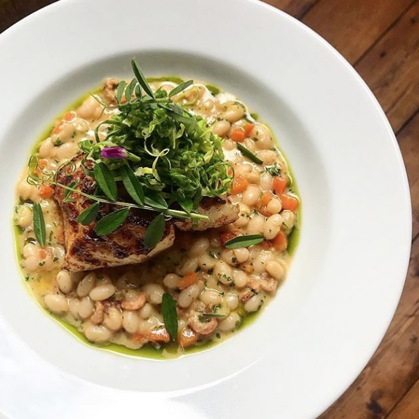 Grilled cod with white bean and brown shrimp cassoulet, image from @clanbrassilhouse on Instagram.